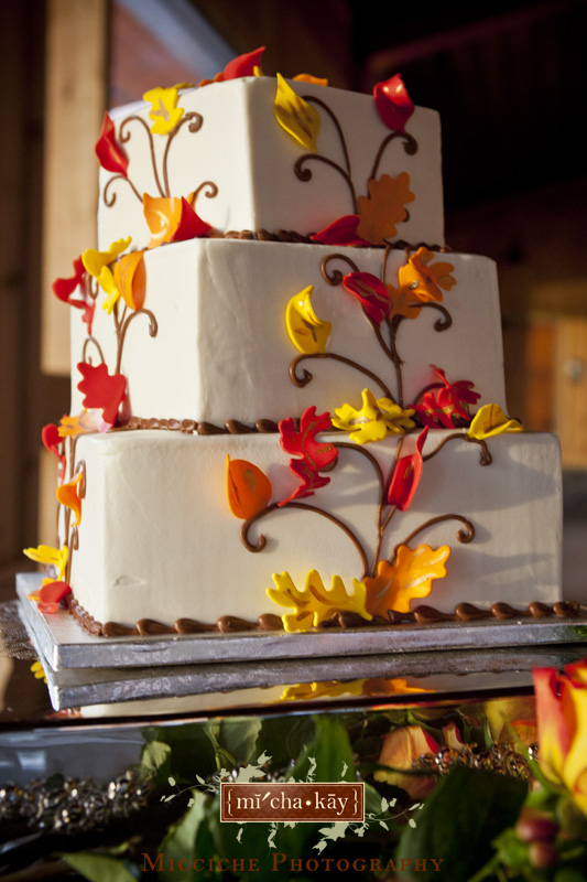 Three tier square wedding cake with orange and yellow leaf details at Autumn Creek Vineyards, a TriadWeddings venue in Mayodan, NC. Image by Mike Micciche Photography, TriadWeddings photographer in Greensboro.