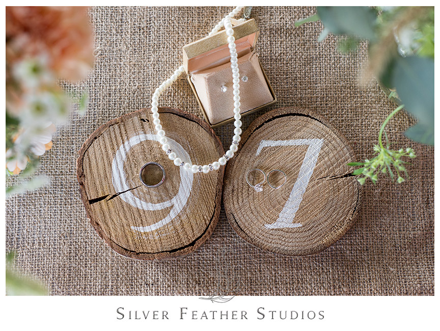 Small logs sliced horizontally make a perfect table number decoration at this Starlight Meadow wedding, a TriadWeddings approved venue. © Image by Silver Feather Studios in Burlington, NC
