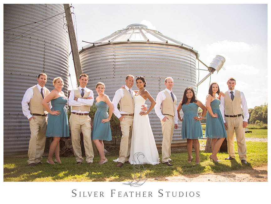 The bridal party complement each other well as they wear their khaki and teal outfits outside of Starlight Meadow, a TriadWeddings venue, along the tall silver silos outside. © Image by Silver Feather Studios, Burlington, NC Wedding Photography and Videography
