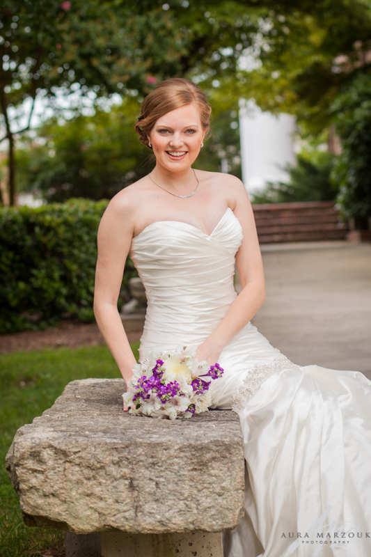 Bride carries a purple and white floral bouquet at her Greensboro College bridal session by Aura Marzouk Photography, a TriadWeddings photography vendor.