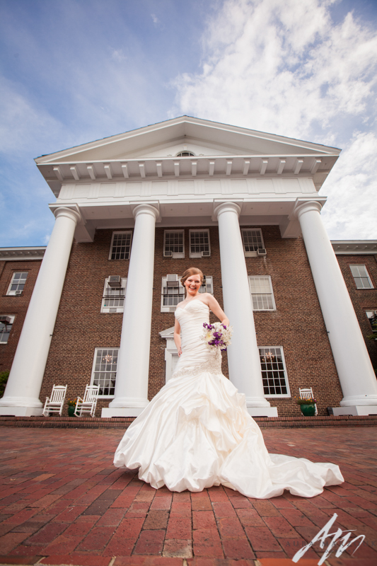 Meghan smiles brightly in front of Greensboro College at her bridal session by Aura Marzouk Photography, a TriadWeddings photography vendor.