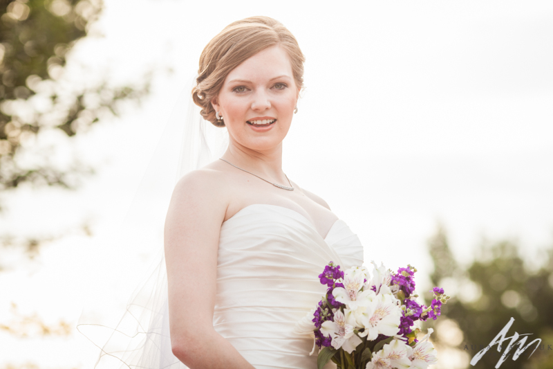 Bride looks stunning with her purple and white bouquet she carries at her Greensboro College bridal session by Aura Marzouk Photography, a Greensboro, NC Wedding Photographer and a TriadWeddings photography vendor.
