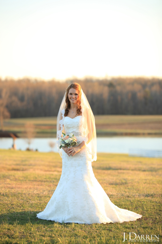 Jennifer holds her ivory and peach bouquet at her Adaumont Farm bridal session with J. Darren Photography, a Greensboro wedding photographer and a TriadWeddings vendor.