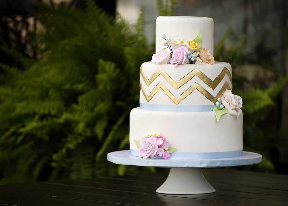 Three tier circle cake with blue ribbon and gold chevron design by Maxie B's, a TriadWeddings magazine vendor.
