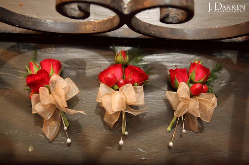 men's boutonnieres, mini red roses, gold bows. Triad wedding at the Lofts at Union Square.