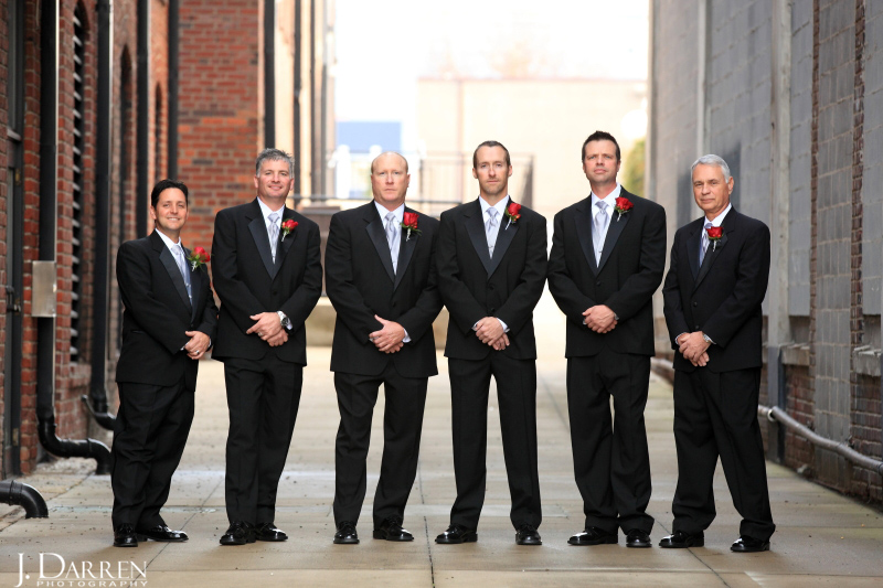 Groomsmen attire; black tuxedoes; silver ties; red rose boutonnieres.