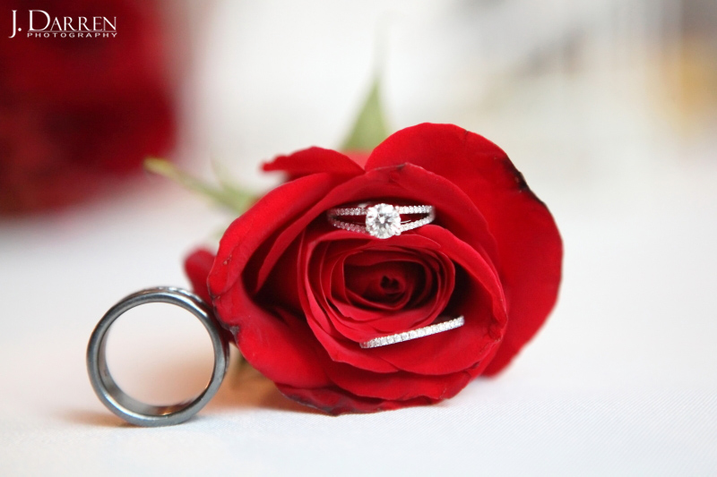 macro image, bridal details, wedding bands and engagement ring, red roses.