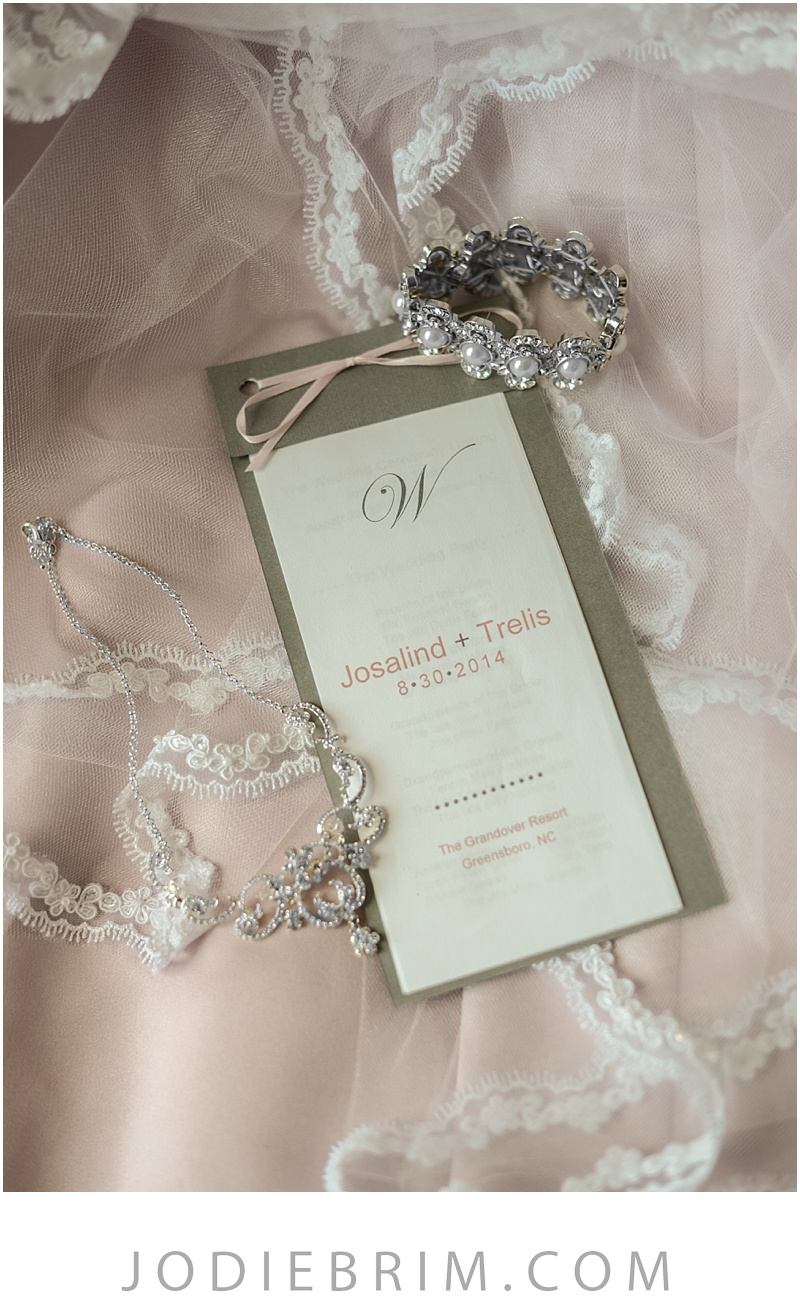 bridal details : lace mantilla veil, rhinestone necklace, and wedding program with pink print.