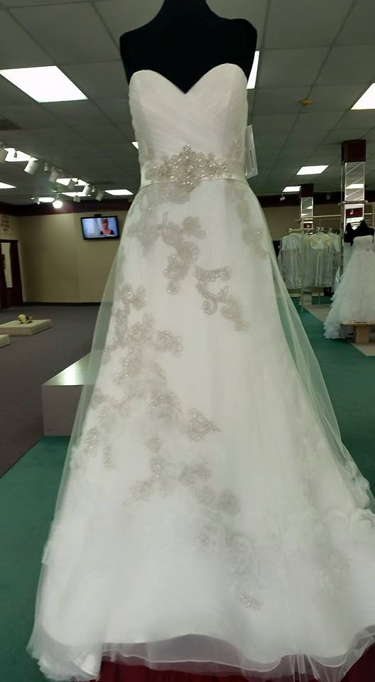 This dress has beautiful details, yet a classic feel. The elegantly detailed empire waist creates the illusion of curves, but is balanced and proportionate.  Photo Credit:  Bridal Mart