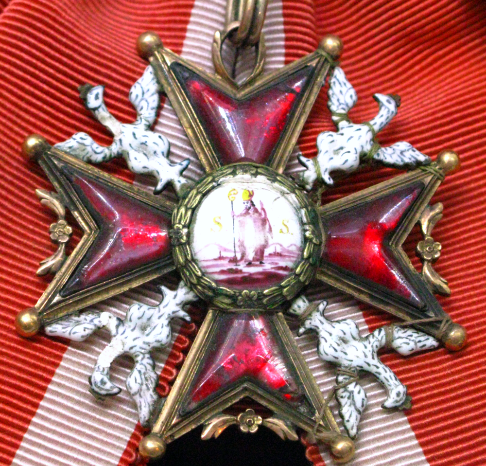 A late 18th century badge of the Polish Royal Order of St. Stanislas with the image of the saint, original Polish white eagles in the axillae, and ruby glass set in the arms of the Maltese cross.