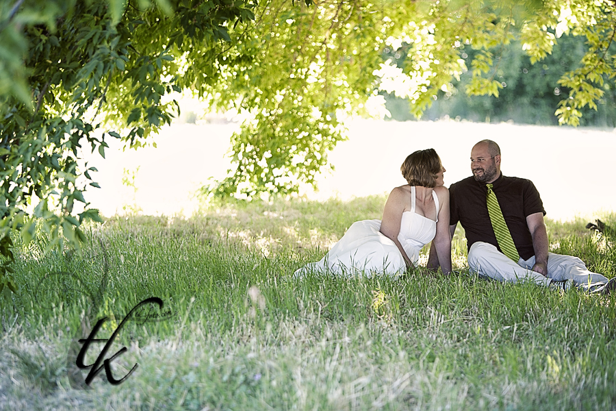 Bride & Groom sitting in a Field - Boise Wedding Photographer