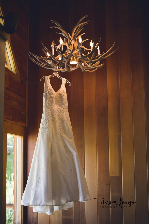 wedding dress hanging from antler chandelier