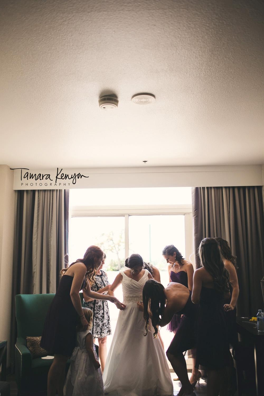 bride putting on dress with bridesmaids boise idaho