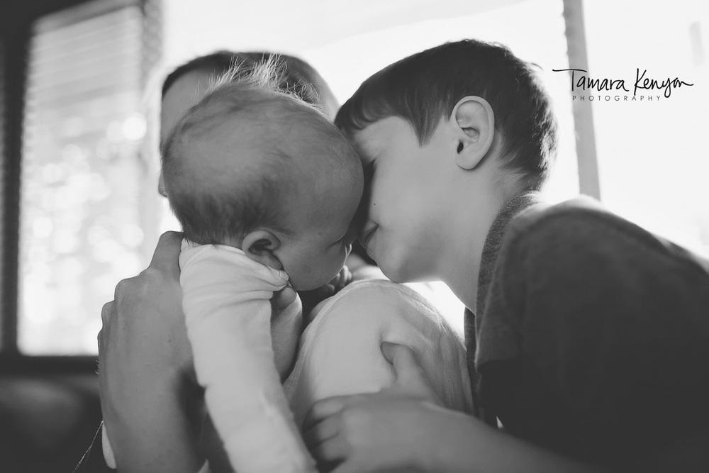 newborn and sibling snuggling