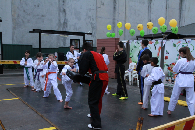 Students demonstrate kicks on the blockpads
