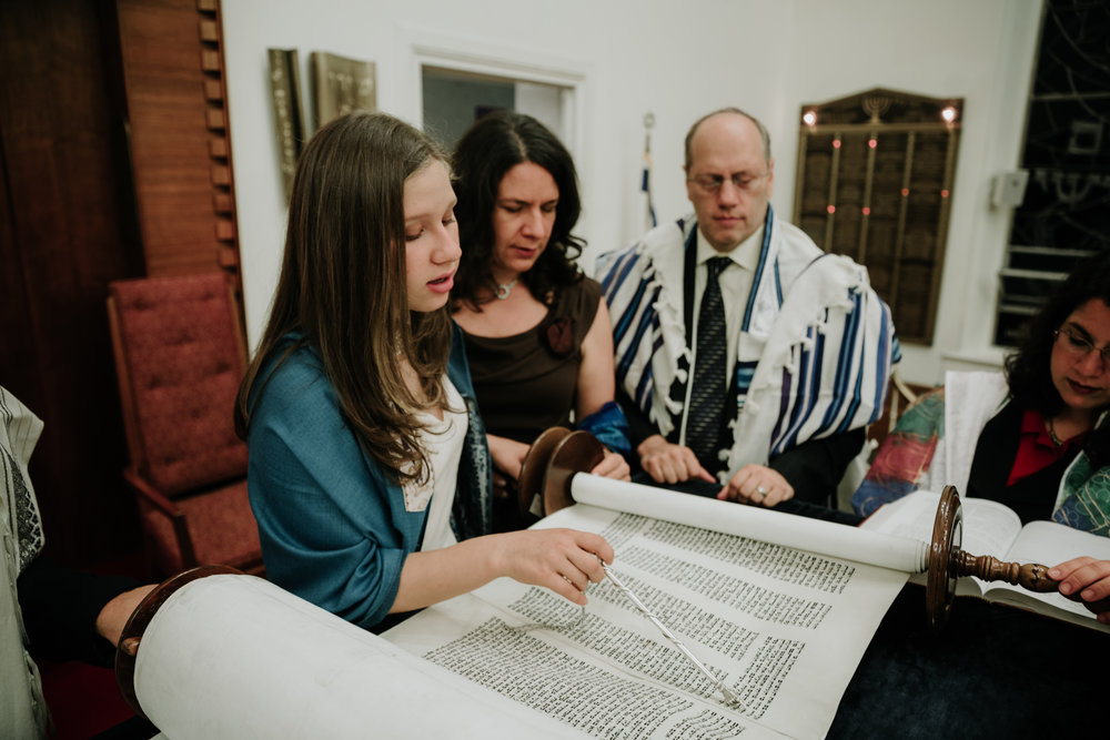 teen-girl-reading-torah-with-parents.jpg