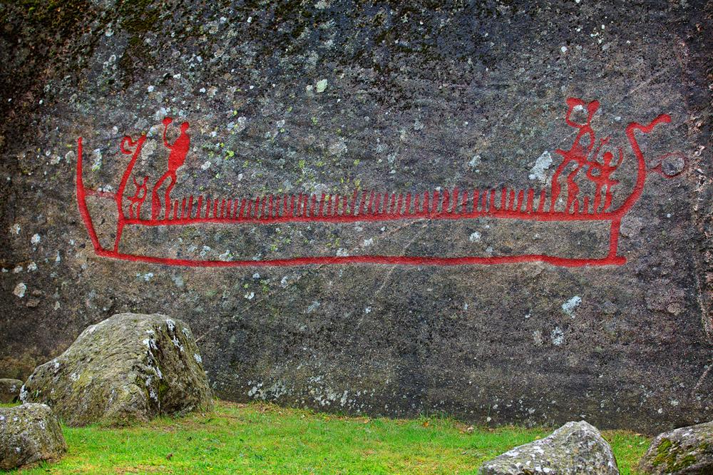 Bjørnstadskipet. Oppe i skipet står to potente menn med hevede økser som følges av hver sin mindre figur. Vi kan tenke oss at dette er høvdingene og deres nærmeste assistenter. I tillegg er det ikke færre enn 48 loddrette streker som vel markerer resten av mannskapet. Det er egnet til ettertanke - fantes det så store skip i bronsealderen? Klikk på bildet for å forstørre bildet.