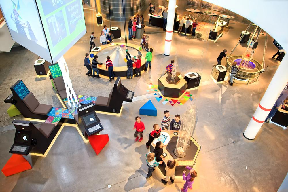 I n  æ  rmest futuristiske omgivelser kan foreg  å  r det meste av aktivitetene med de interaktive utstillingene. Her kan du blant annet rulle opp en rakett h  ø  yt, h  ø  yt til v  æ  rs f  ø  r den daler ned i fallskjerm.  Klikk på bildet for å forstørre.