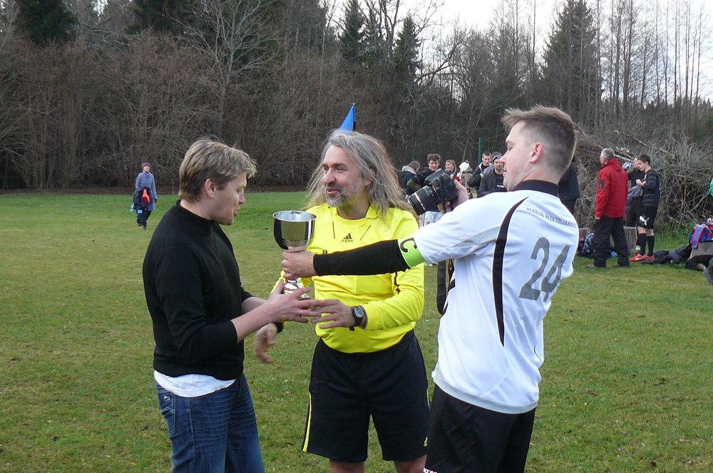 Aivar Pohlak awarding FC Taritu with the RL trophy after a tight win at penalties (Jalgpall.ee/Alver Kivi)