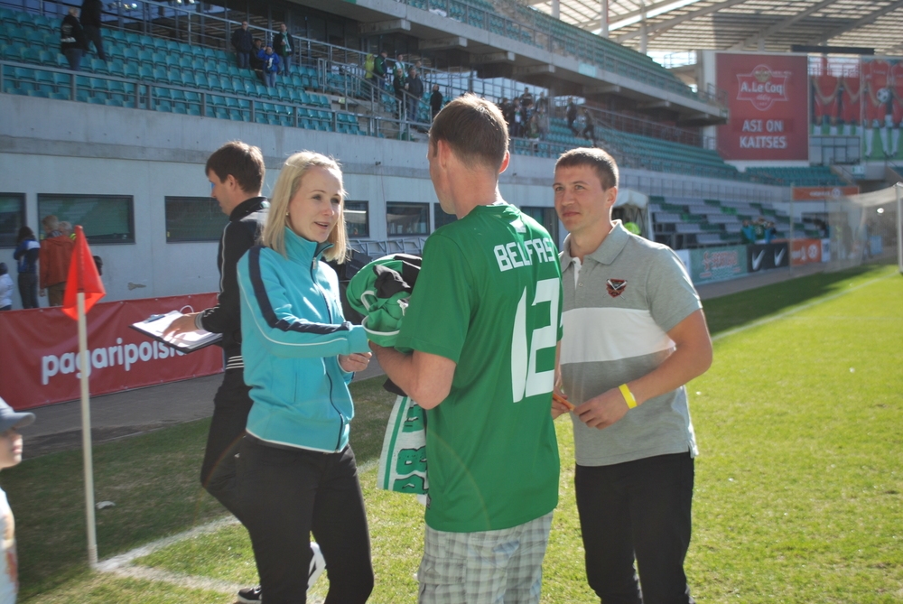 FC Flora CEO, Reili Järvalt, awards a fan with a prize after an interval shooting challenge