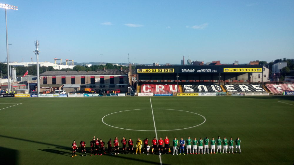The teams line up in glorious sunshine, with the famous Belfast docks visible in the distance.