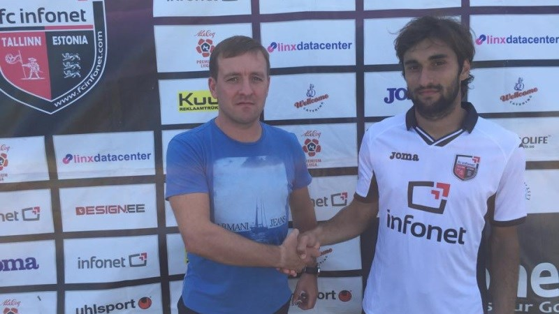 Tumasjan shakes hands with club's official, Altosaar, in his new club's jersey.
