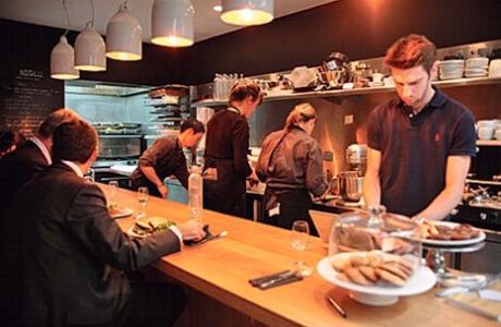 오픈 키친으로  1  층에는 바  , 2  층에는 테이블이 놓여 있다  .