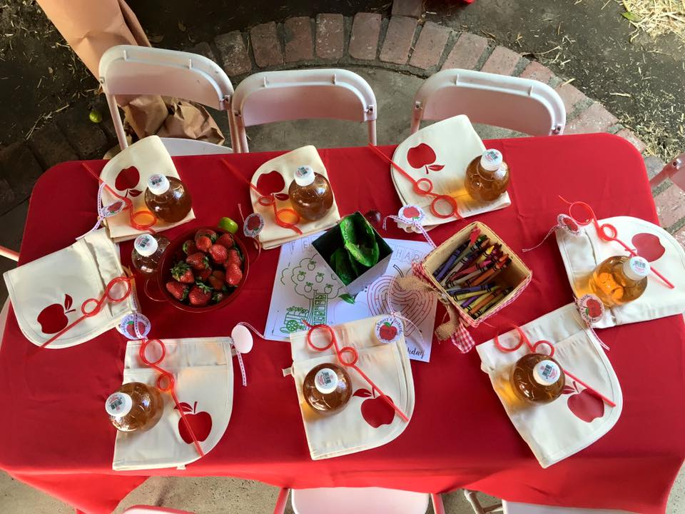 Apple Orchard Party Kid's Table: berry colander with strawberries, berry basket with crayons, coloring sheets, twisty straws, apple juice, apple aprons (made by Down Emery Lane) and treats.