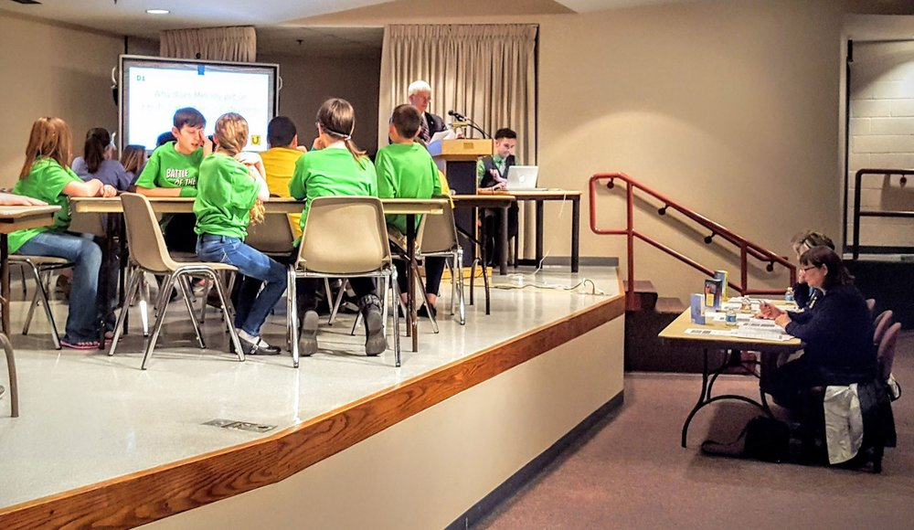 Superintendent of Zanesville City Schools, Dr. Doug Baker, reads aloud a question during Round 2 of the 2016 Battle of the Books competition.