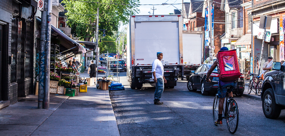 Bike courier vs delivery truck in Kensington Market, Toronto.
