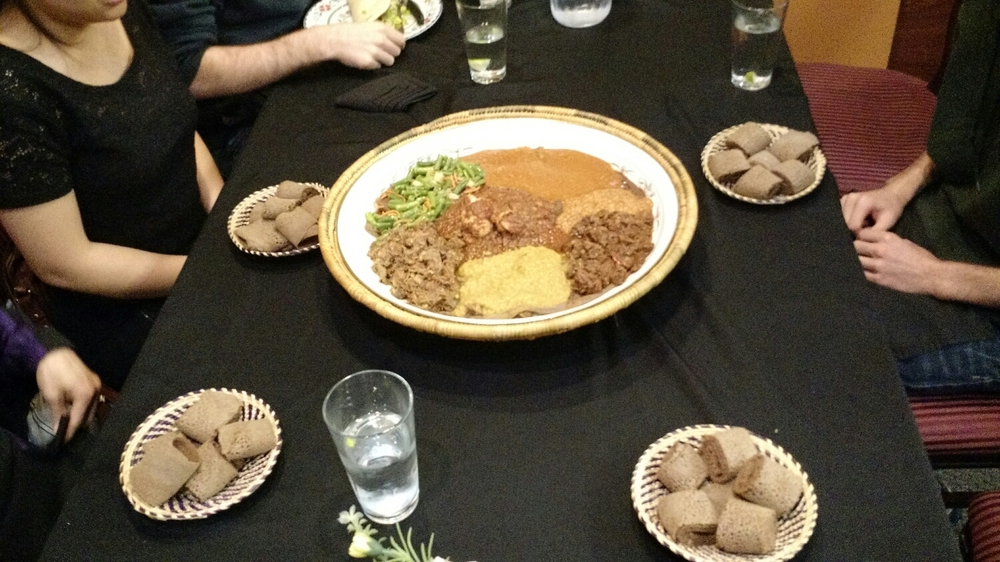 Family-style dish with individual plates of injera.