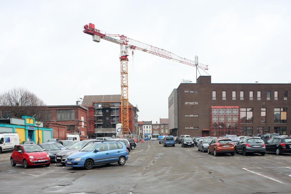 Vue depuis le parking vers la Place Destrée et la Chaussée de Lodelinsart. A droite, la Maison communale annexe, à gauche les accès aux établissements scolaires (photographe:  Maxime Delvaux ).