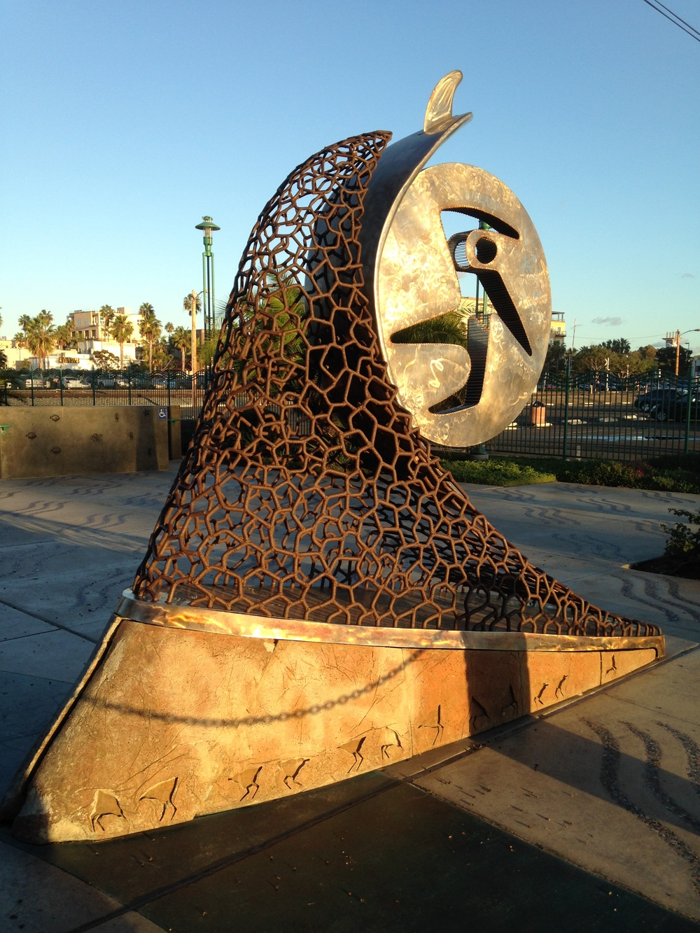 This surfing sculpture is located near the pier.