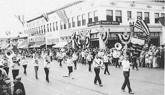 The Santa Ana Polytechnic High School band marching in a parade in front of the Phillips Hutton Building in the early 20th century