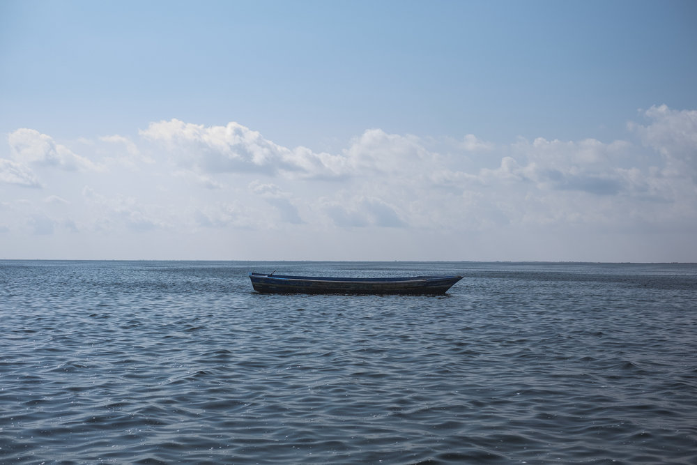 Abandoned wooden boat just off the coast of Tunisia. Boats like these are often shared between 80–100 people. Many die either because of the exhaust fumes or by drowning before they reach Europe.