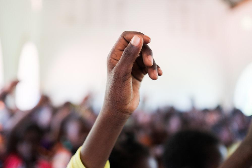 Kids raise their hands in a classroom that was repaired by Finn Church Aid. Berberati, Central African Republic, 2017.