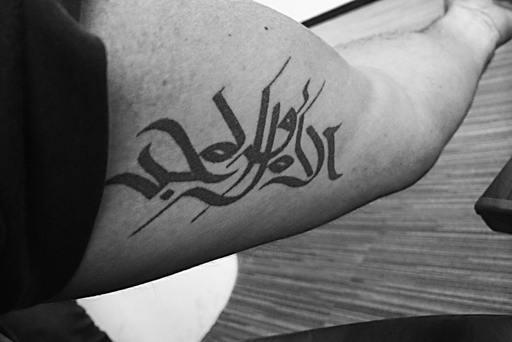 Name:   Richard Nugent       Designed  by  Wissam Shawkat and myself.      Meaning:   I t means HOPE AND GLORY, although fairly difficult to read because of the style i chose this phrase as it's a very British statement and as a British National i moved to Dubai 9 years ago and wen't through alot of up's and downs before successfully meeting my wife and building a wonderful family, this part of the world is very special to me and the tattoo was done to mark this time and region!
