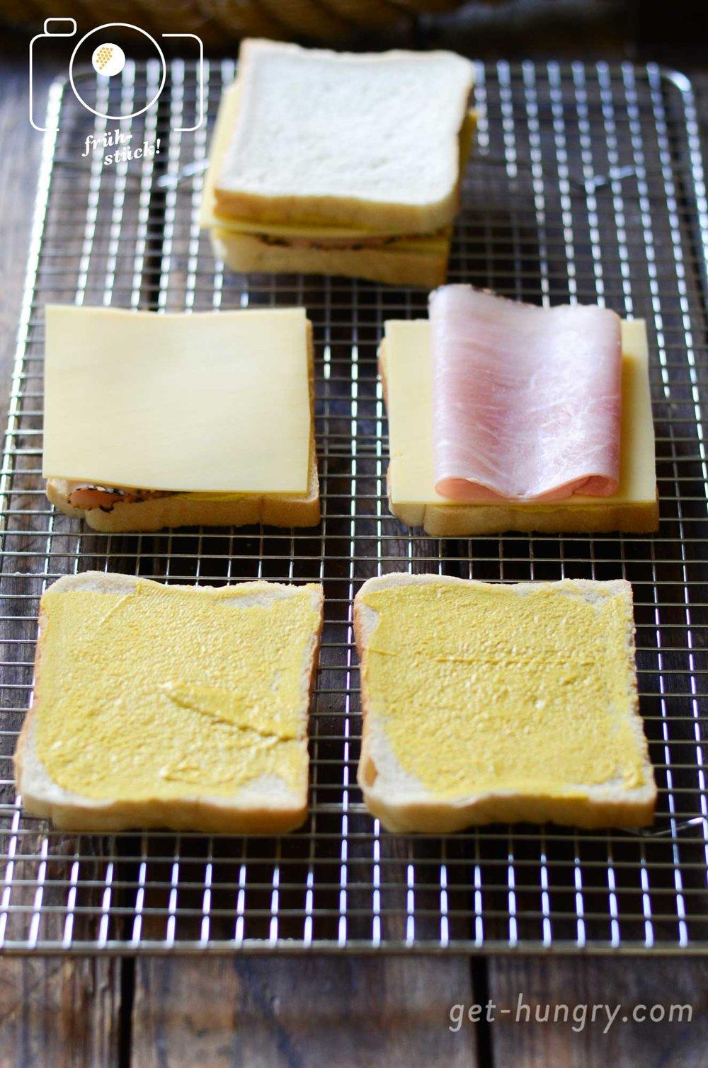 Brot wird mit Senf, Schinken und Käse doppelt gestapelt.