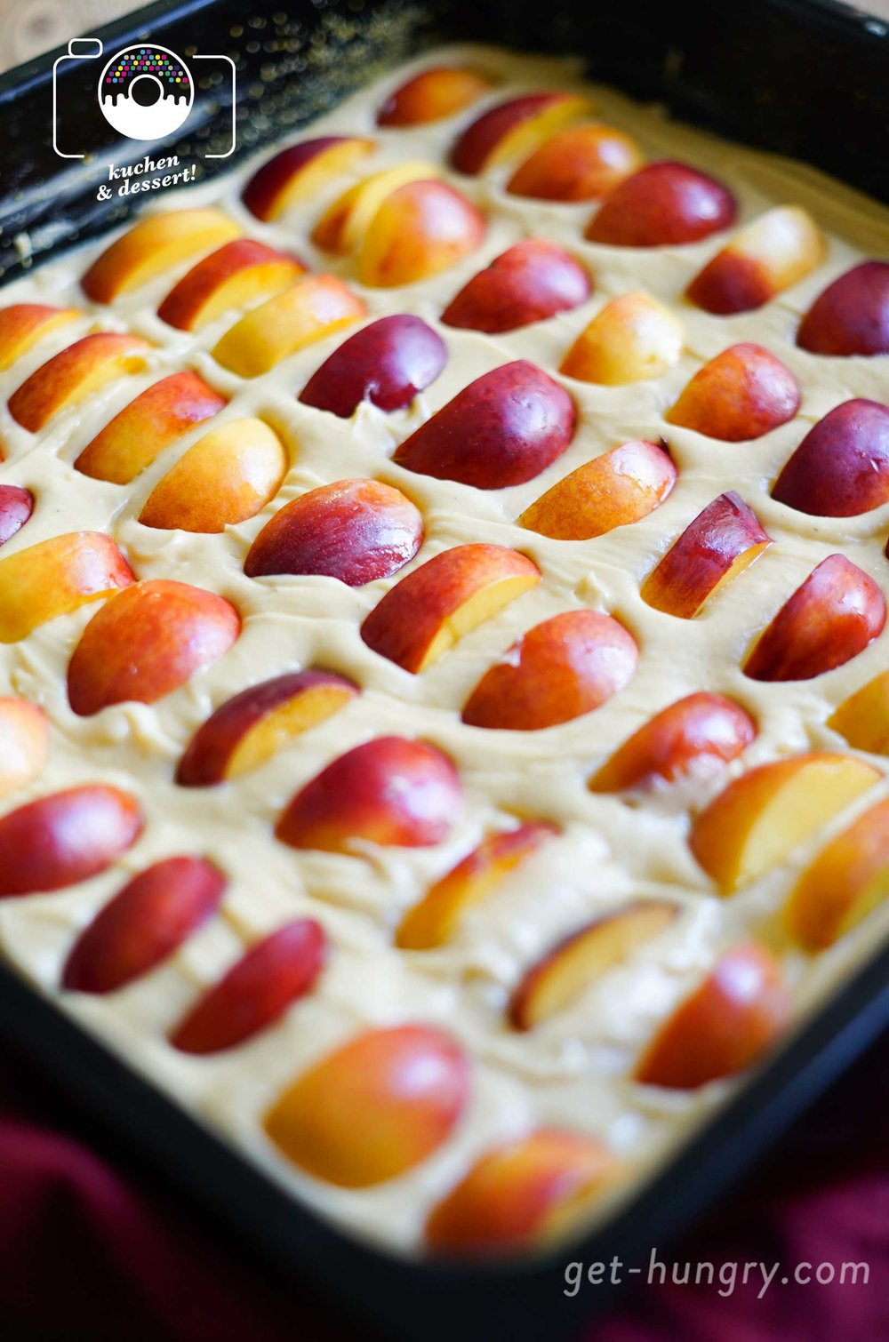 Die Früchte in regelmässigem Abstand, aber durchaus eng in den glatt gestrichenen Teig versenken.