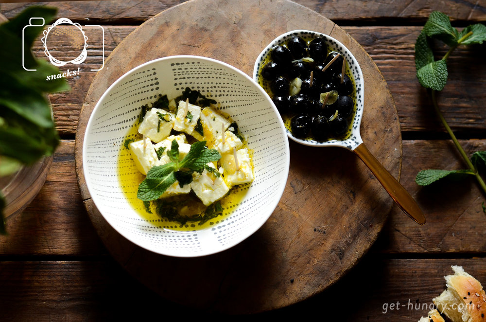 Feta und Oliven im warmen Zitronen-Knoblauchöl mariniert - Klassiker mit Fahne.Für einen Block Feta (200g) und ein Glas schwarze entkernte Oliven mixt du folgende Marinade: 10 EL Olivenöl, 2 Zehen Knoblauch blättrig geschnitten, 1 TL Abrieb einer Bio-Zitrone. Öl bei mässiger Hitze erwärmen, für 10 Minuten ziehen, danach abkühlen lassen. Die Marinade über Schafskäse und Oliven gießen (können ruhig eine Zeit lang darin baden). Feta mit gehackter Minze bestreuen und einstellen.