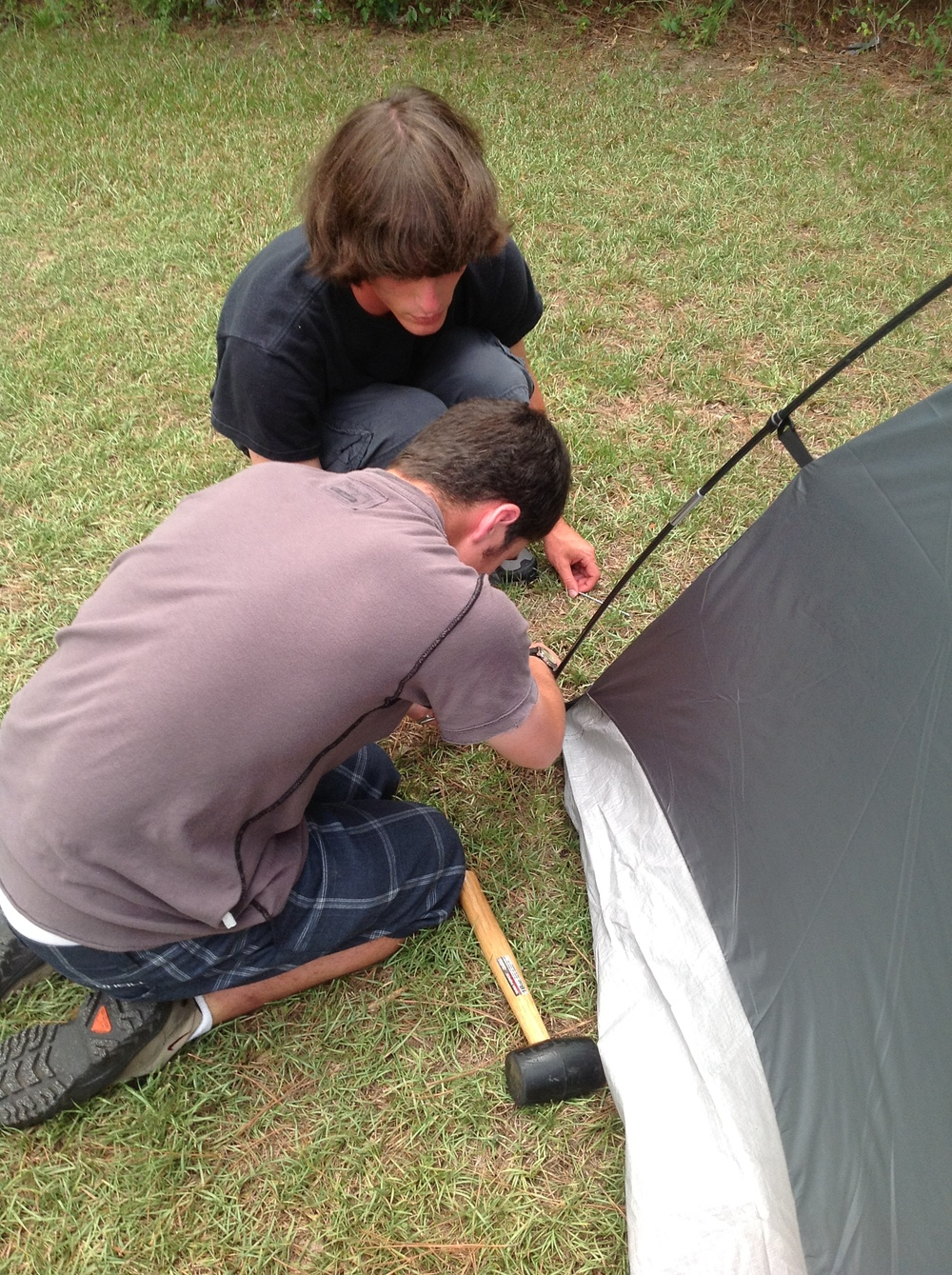 Ben (counselor) and Matthew ensure that the tent is secure.