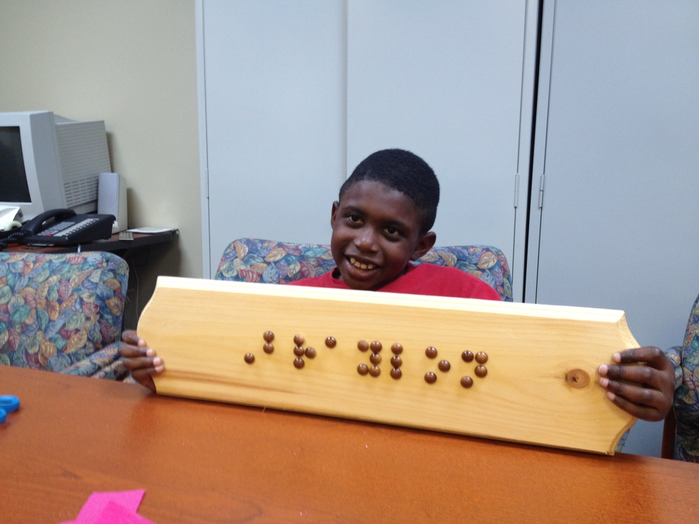 Braylon shows off his braille name plate made during the 2013 NFB BELL program