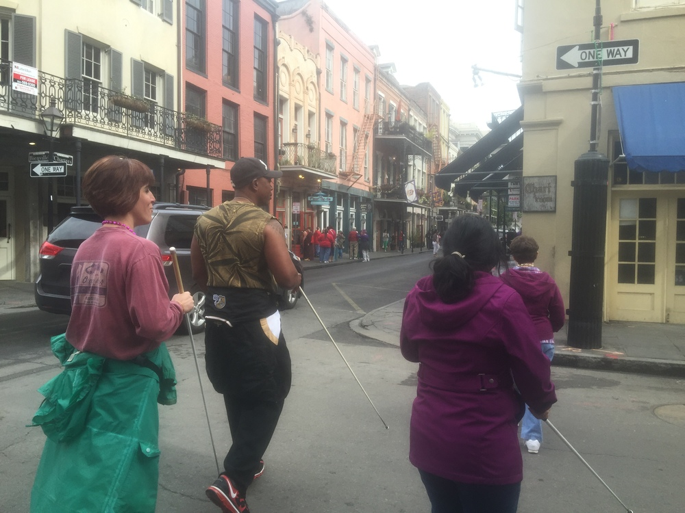 Image shows staff and students crossing Bienville St