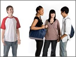 Teens: one is looking at a group of three other socializing