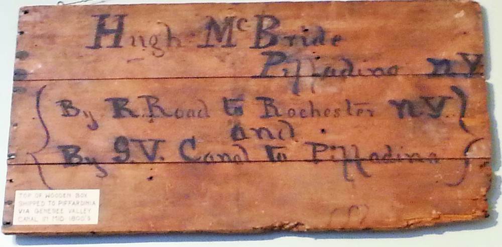 The top of this wooden box shows that a box was shipped to Hugh McBride via the Genesee Valley Canal to what is now known as Piffard (originally named Piffardinia and misspelled here as Piffardina). The Genesee Valley Canal was open from 1840-1878 and eventually connected the Erie Canal at Rochester to the Allegheny River in Pennsylvania.  Although it never proved to be a profitable venture, the canal was important in carrying agricultural goods and raw materials out of the area and in bringing manufactured goods and new settlers into the Valley.