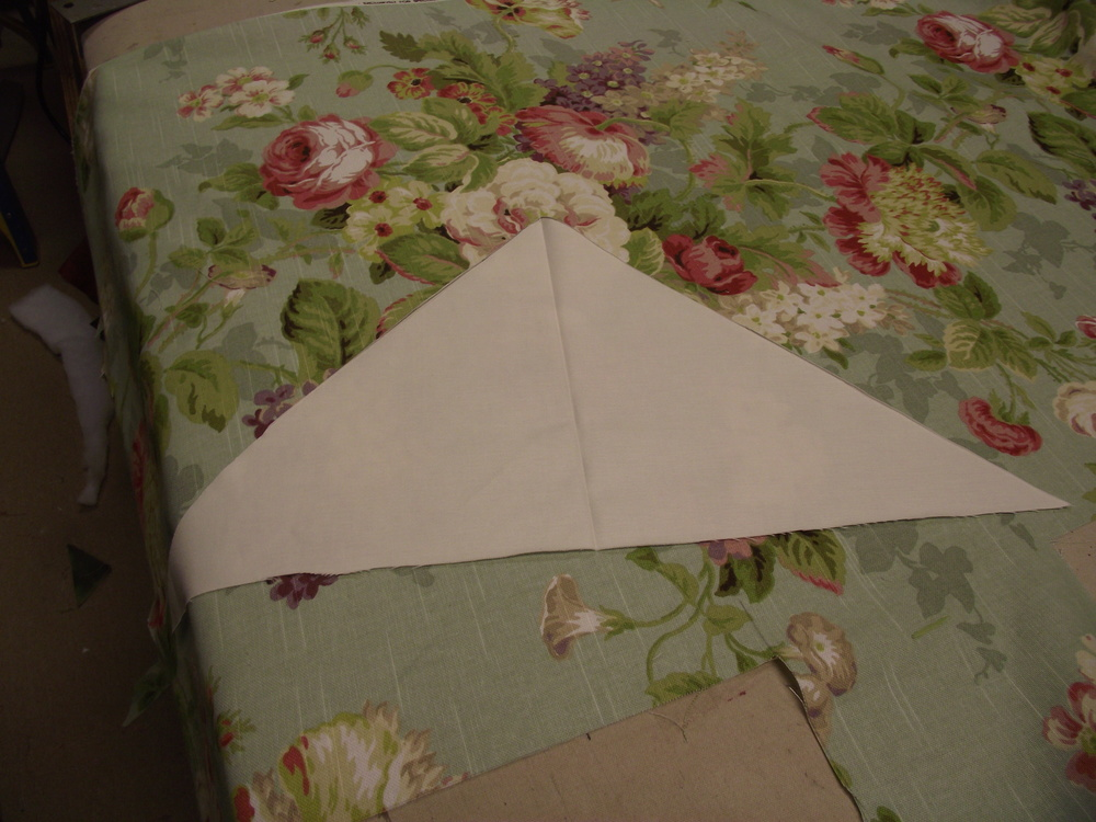 Pattern laid over floral fabric. When Mitering patterns other than stripes it is important to place the pattern properly before cutting.  In this example I elected to have the dominate white flower become the center of the finished face piece.  Next the triangle was positioned and re-positioned until I had a bold recognizable flower on both the left and right side.   This is very important for the effect to work.