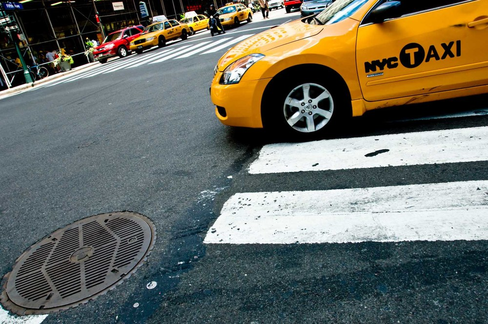 Down the drain yellow cab nyc taxi new york city manhattan car sidewalk cross road stop downtown.jpg