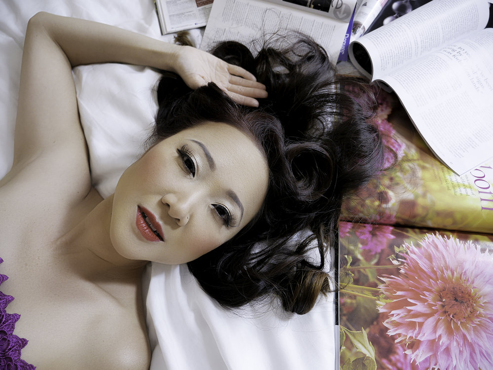 Boudoir portrait of Asian woman on bed with flowers
