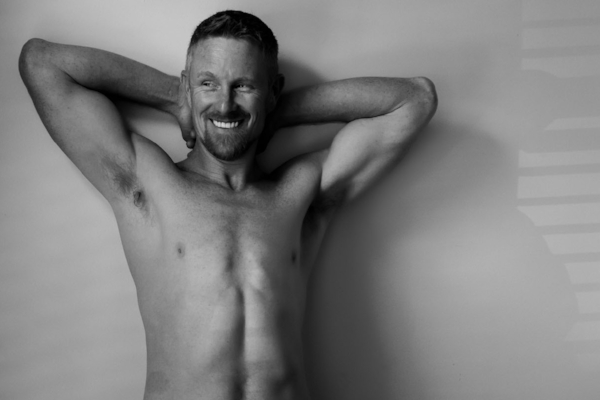 Male Boudoir Man Smiles with Arms Raised.jpg