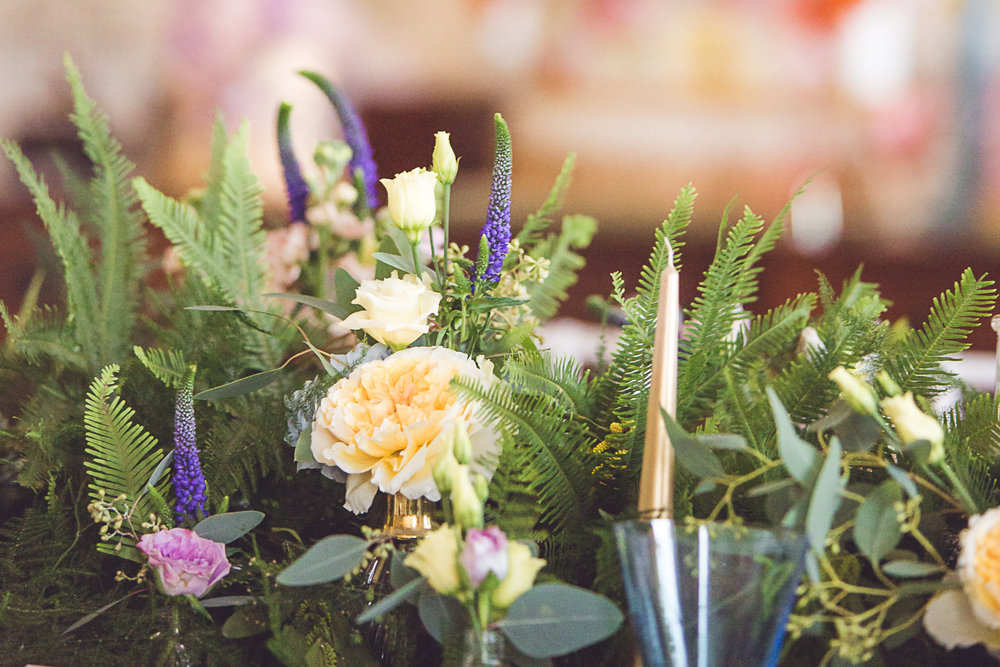 A mix of bright florals sit amongst abundant foliage, with the brides bouquet tying in perfectly with the table styling